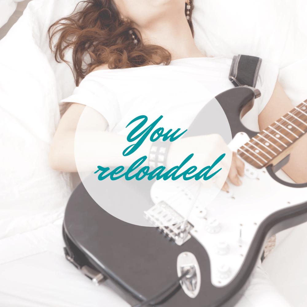 You reloaded - Person liegt mit E-Gitarre auf Bett und hat Hand an den Seiten