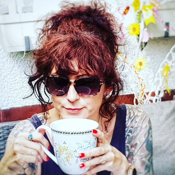 Portrait Violetta Braimovic - trinkt Tee, hat Sonnebrille auf, sitzt draußen