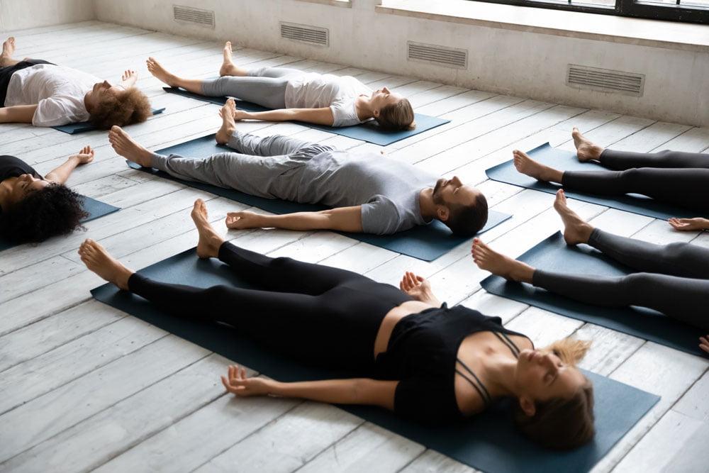 Richtig entspannen bei Stress, mehrere Personen in einem ENtspannungskurs - liegen ausgestreckt auf Matten und haben die Augen geschlossen
