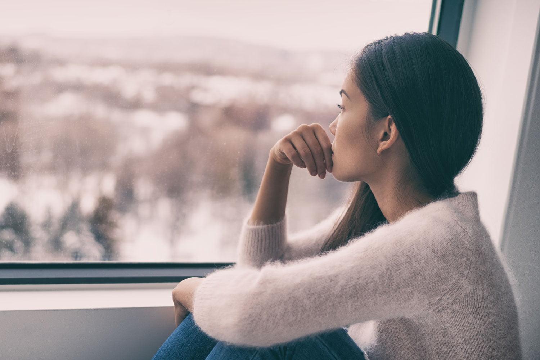 Frau mit Winterdepression am Fenster